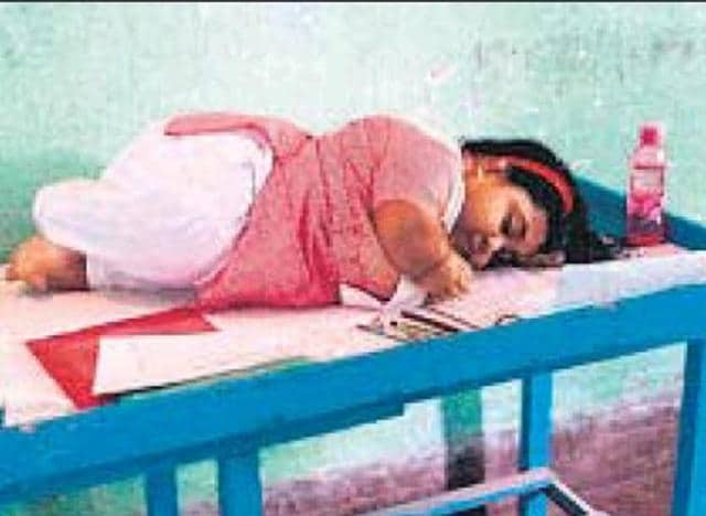 Piyasha Mahaldar, who suffers from achondroplasia, writes her exam.