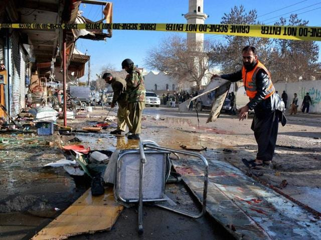Pakistani security officials examine at the site of suicide bombing in Quetta, Pakistan, Wednesday, Jan 13, 2016. The suicide attack on a polio vaccination center in southwestern Pakistan killed more than a dozen people and wounded many, officials said.