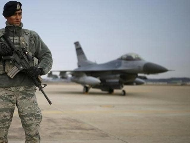 A US soldier stands guard in front of a  F-16 fighter jet. India had expressed displeasure over the Obama administration's decision to sell these nuclear-capable jets to Pakistan.