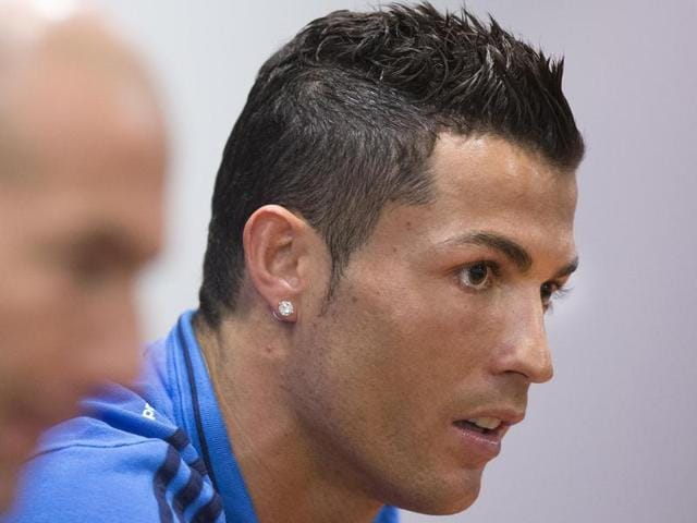 Real Madrid's Cristiano Ronaldo speaks during a press conference in Rome on February 16, 2016, ahead of the Champions League match against AS Roma. In foreground is Real Madrid coach Zinedine Zidane.