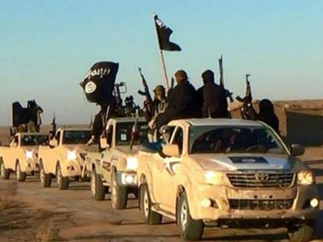 """Militants of the Islamic State group are seen holding up their weapons and waving IS flags in Syria in this undated file photo released online in the summer of 2014 on a militant social media account. The extremist group that once bragged about minting its own currency is now accepting only US dollars in Raqqa, slashing salaries across the board and imposing """"exit fees"""" for those trying to leave its domain."""