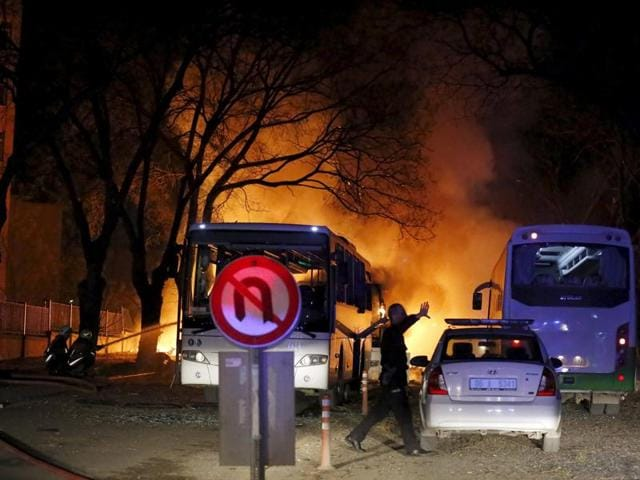 A police officer gestures as he walks at the explosion site in Ankara.