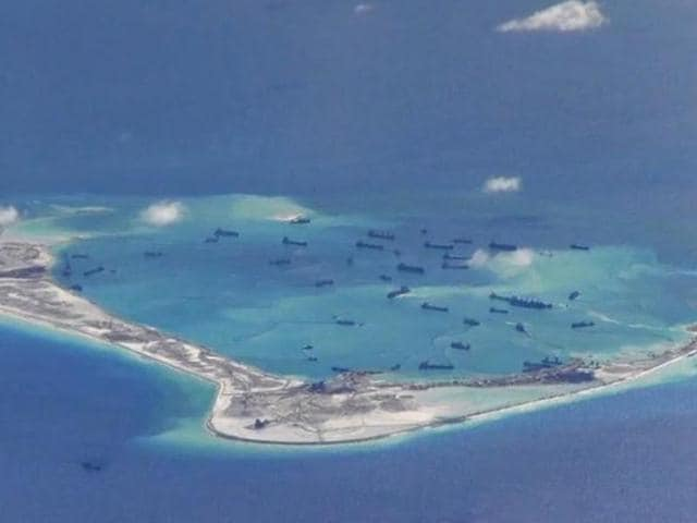 Chinese dredging vessels are purportedly seen in the waters around Mischief Reef in the disputed Spratly Islands in the South China Sea in this still image from video taken by a P-8A Poseidon surveillance aircraft provided by the United States Navy.(US Navy Handout Image)