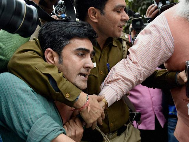 A policeman tries to save a JNU student who was being beaten up during a clash between the advocates and the students outside the Patiala House Courts in New Delhi on Monday.