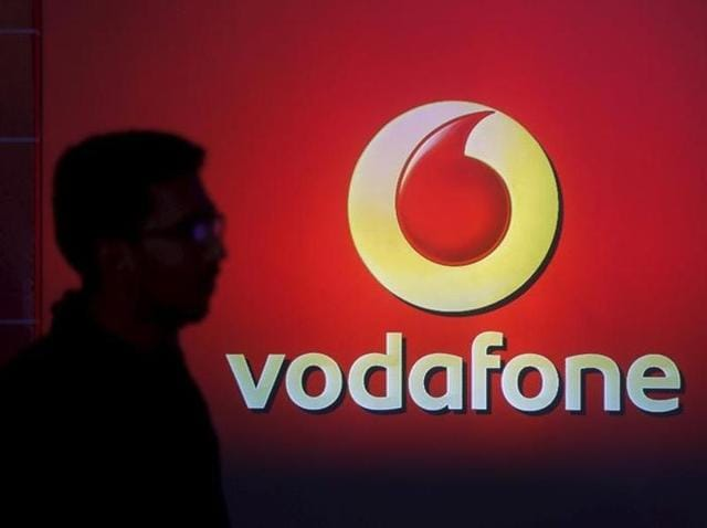 A street vendor walks past a Vodafone outlet in New Delhi. The British telecommunications group expressed its intention to be a long term investor in India.