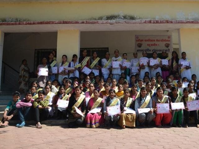 A group of girls poses with Miss Haemoglobin crown and certificates at an anganwadi in Mhow sector.