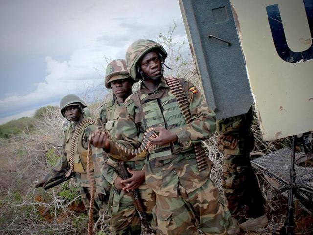 Soldiers stand next to an armoured carrier during an  operation to seize and liberate territories from Al-Shabaab militants in Deyniile.