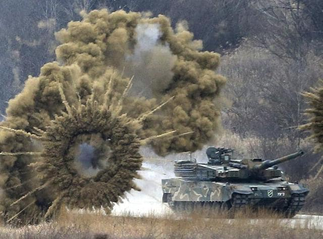 Smoke bombs explode near a South Korean army K-2 tank during a live firing drill at a fire training field in Yangpyeong, South Korea.