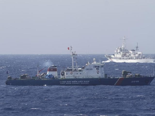 A ship (top) of the Chinese Coast Guard is seen near a ship of the Vietnam Marine Guard in the South China Sea, about 210 km (130 miles) off the shore of Vietnam, in this May 14, 2014 file photo.