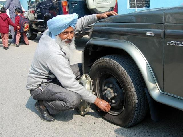 A member of the Government Driver and Technical Employees Union deflating a tyre of ADC Shina Aggarwal's vehicle in Bathinda on Thursday.