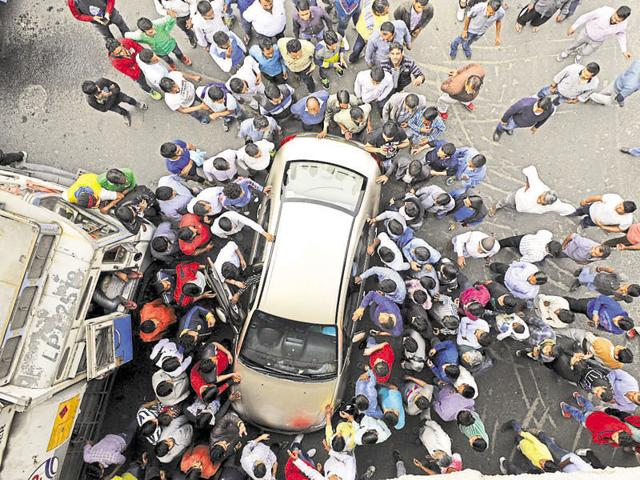 Protesters attack a vehicle at Bakhtawar Chowk on Friday.