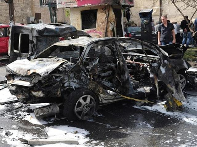 At least 25 people were killed in twin car bomb blasts that hit the Syrian city of Homs.
