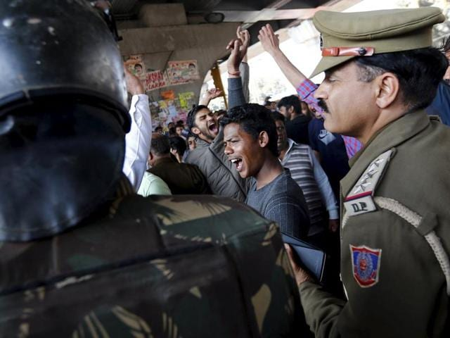 Demonstrators from the Jat community shout slogans next to police during a protest in New Delhi.