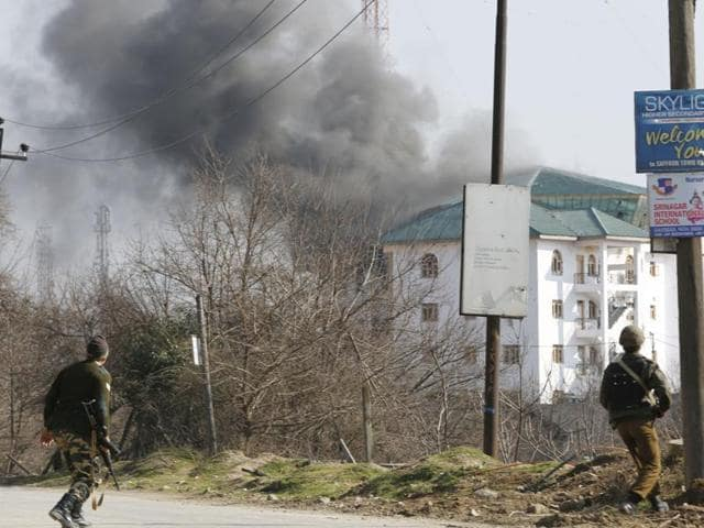 Security personnel take position near the building where suspected militants have taken refuge during a gun battle on the outskirts of Srinagar.