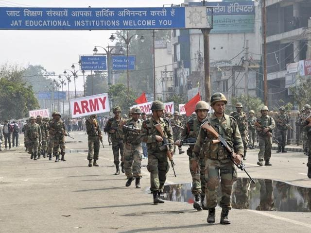 Indian army soldiers conduct a flag march at Rohtak.