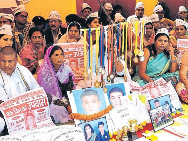 Vinay Mahto's parents sit on a dharna organised by the Aam Aadmi Party near Governor's House in Ranchi on Sunday.
