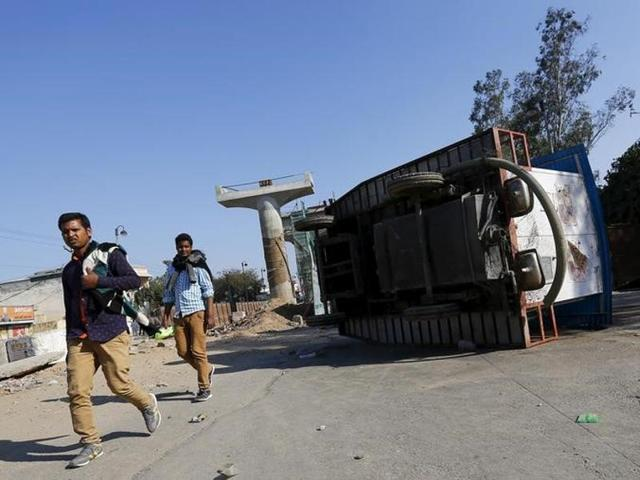 People walk past an overturned mobile urinal during a demonstration by members of the Jat community in Bahadurgarh in Haryana.
