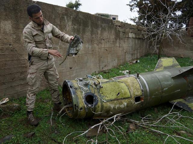 A rebel fighter inspects a piece of a rocket that landed in an area that connects the northern countryside of Deraa and Quneitra in Syria.