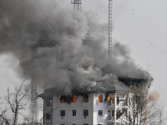 Columns of smoke come out from the top floor of building which militants were holed up during a gunfight in  Pampore, some 15 km south of Srinagar.