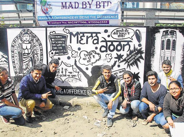 Members of Making A Difference By Being The Difference in front of the wall mural in Dehradun on Monday.