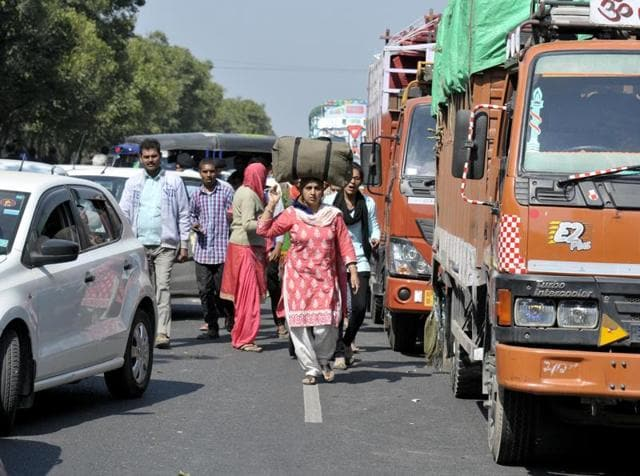People walking during a blockade by Jat protesters at Ladsoli village in Sonepat district on Monday.