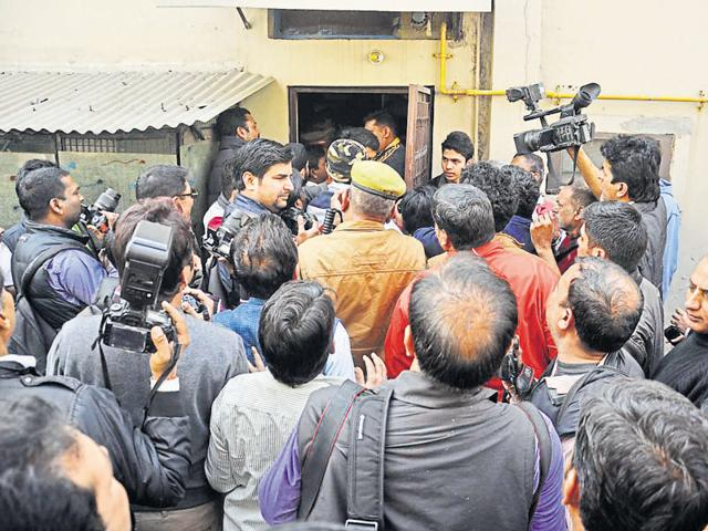 Police and media personnel outside the residence of the victim on the day after the abduction. A police officer said a gunner has been provided there for her family's security.