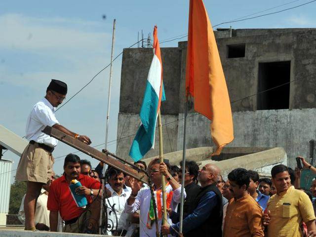 Congress party leaders, led by state president Arun Yadav, hoist the national flag at the Indore RSS office.