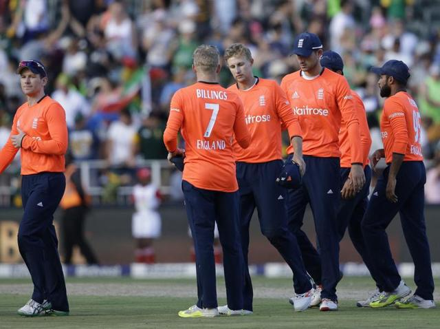 England's captain Eoin Morgan, left, with teammates leave the field after losing the second and final T20 match against South Africa at the Wanderers Stadium in Johannesburg on February 21, 2016.