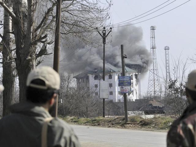 Soldiers stand guard near the encounter site in Pampore.