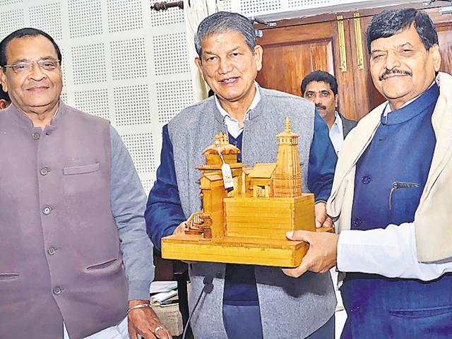 Uttarakhand CM giving a memento to UP minister Shivpal Yadav.