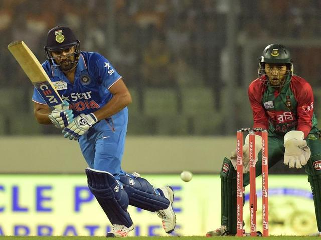 Indian cricketer Rohit Sharma (L) is watched by Bangladesh wicketkeeper Mushfiqur Rahim as he plays a shot during the T20 match between India and Bangladesh in the Asia Cup in Dhaka on February 24, 2016.