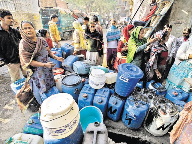People wait to fetch water from municipal tankers in New Delhi on Tuesday.
