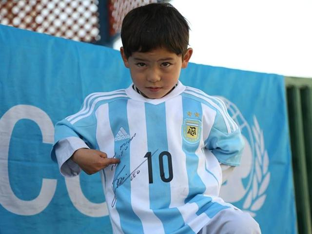 Afghan boy Murtaza Ahmadi, who became an online sensation by wearing a plastic shirt with Lionel Messi's name on it, seen with the jersey sent to him by the Argentine footballer.