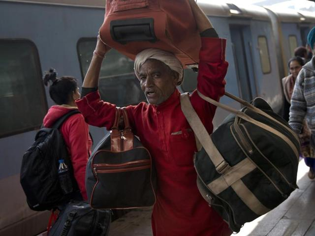 A porter carries bags of a passenger at a train station in Delhi. Railway minister Suresh Prabhu Thursday unveiled the budget for one of the world's largest railways network.