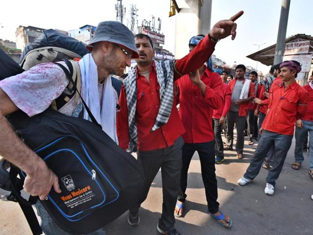 Railway porters at New Delhi railway station seek to assist a passenger. Porters will now be known as 'sahayaks', not coolies.