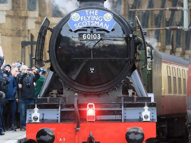 People watch from a railway platform as the Flying Scotsman steam engine prepares to leave Kings Cross station in London.