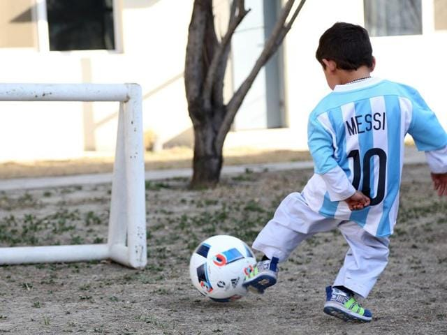 This handout photographby Unicef Afghanistan shows five-year-old Afghan boy Murtaza Ahmadi posing with a jersey sent to him by Argentine football star Lionel Messi.