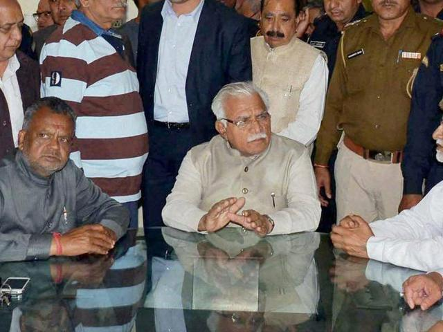 Haryana chief minister Manohar Lal Khattar speaks with people affected by the Jat agitation, in Rohtak.