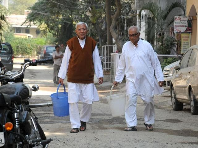 Baldev Raj Kapoor (left) and RK Sharma, both heart patients, carry water on Friday morning in DLF Phase 3.(Parveen Kumar/HT Photo)
