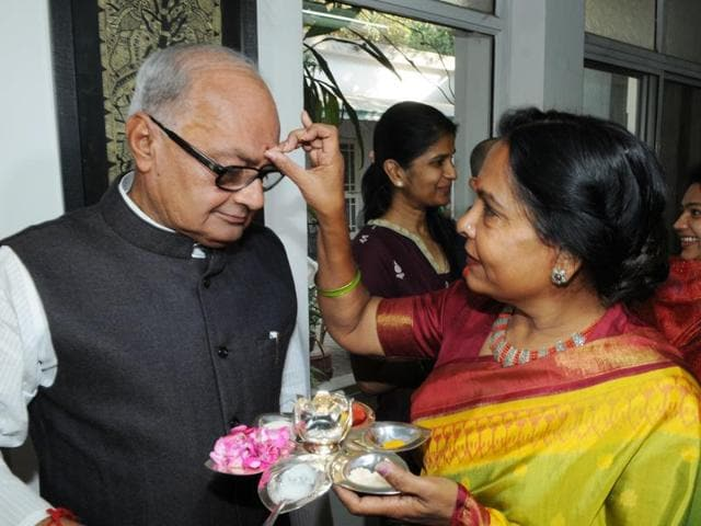 Finance Minister Jayant Malaiya's wife Sudha Malaiya  applies tilak on the minister's forehead before he left for presenting the state budget, in Bhopal on Friday, February 26, 2016.