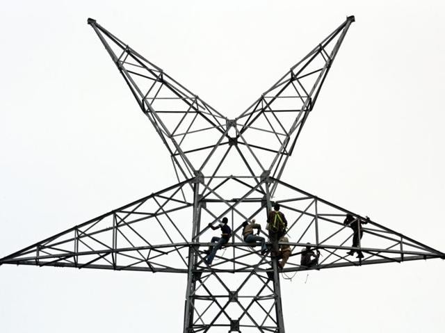 Workers repair electric cables. Power tariffs may be in for rationalisation.