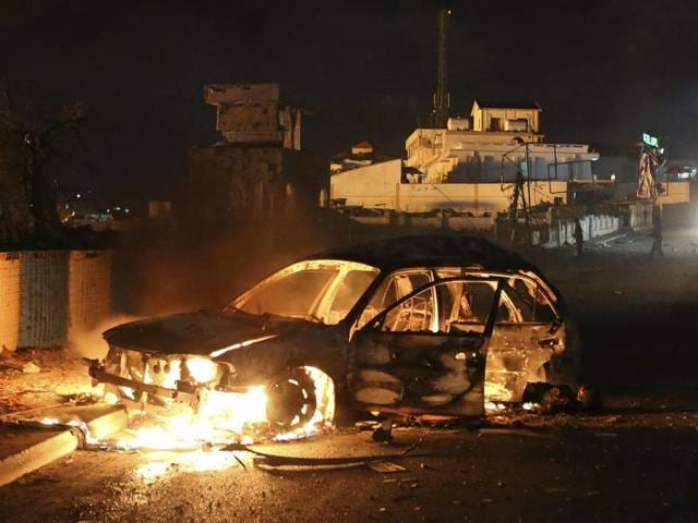 A car suspected by the Somali police to have been used in a bomb attack burns along a street near a hotel in Hamarweyne district in capital Mogadishu.