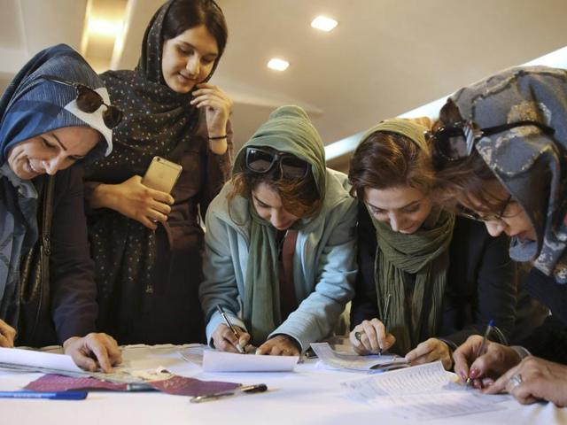Iranian voters fill out their ballots during the parliamentary and Experts Assembly elections in a polling station in Tehran, Iran.