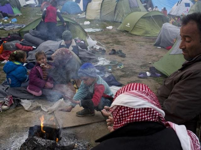Stranded refugees from Iraq sit next to a makeshift fire while waiting to be allowed to cross the Greek-Macedonian border near the northern Greek village of Idomeni, Sunday, Feb. 28, 2016.