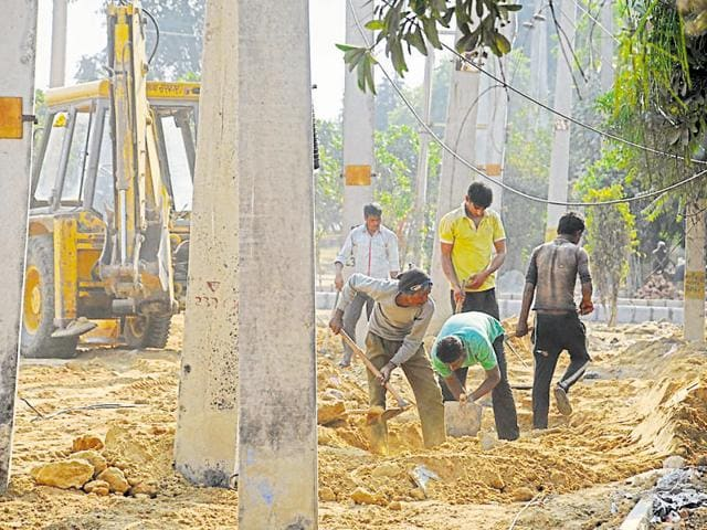 Workers remove construction debris from a green belt near CyberHub ahead of the investors' summit.