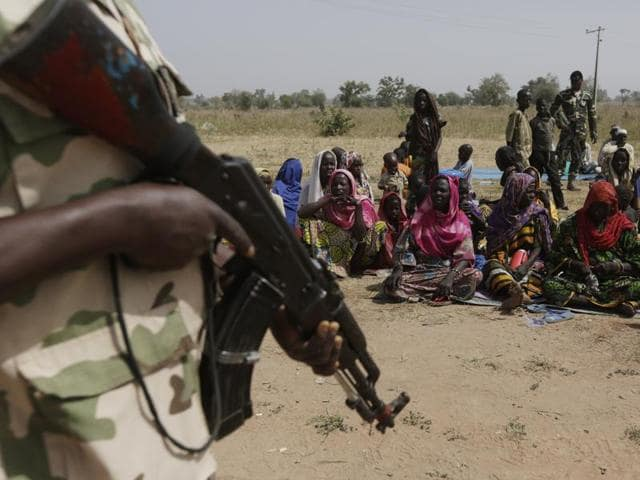 In this December 8, 2015 file photo, soldiers guard people fleeing from Boko Haram's carnage and about to be searched to ensure there are no insurgents infiltrating a refugee camp. Cameroonian and Nigerian forces have freed several hundred hostages in a border town held by Boko Haram, the commander of Cameroonian forces said on Saturday.