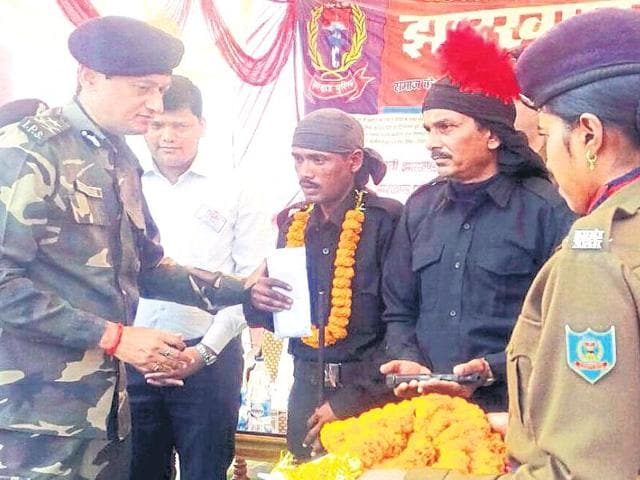 Two Maoist rebels surrender along with their weapons before police in Chatra on Sunday.