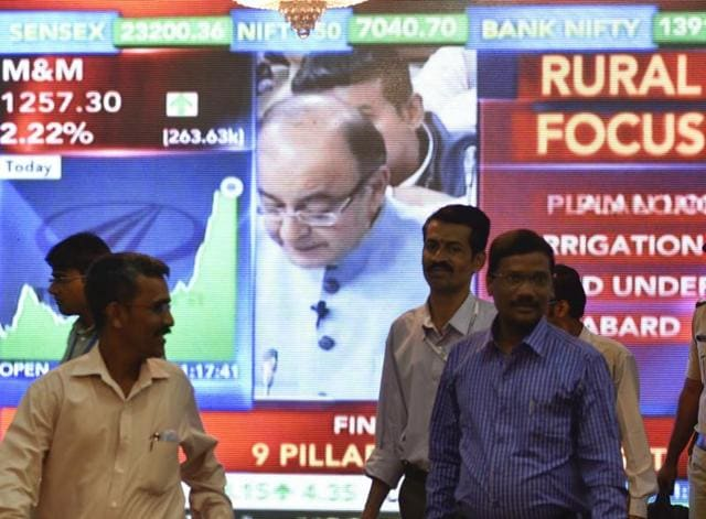 Office-goers walk past a digital screen showing finance minister Arun Jaitley delivering his Budget speech at Parliament in New Delhi on February 29, 2016.