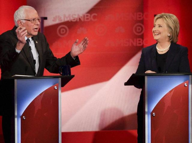 Democratic presidential candidates Hillary Clinton and Bernie Sanders interact during a primary debate at the University of New Hampshire.