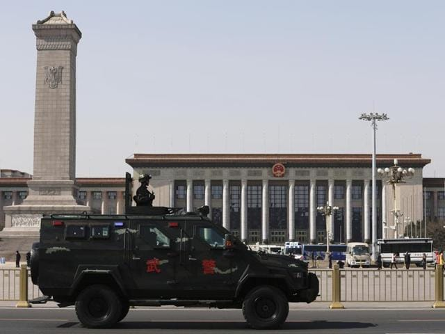 """An armed Chinese paramilitary policeman standing atop an armored vehicle patrols past Tiananmen Square and the Great Hall of the People, ahead of a national political conclave  in Beijing, Monday. Chinese businessman Ren Zhiqiang, nicknamed """"the Cannon"""", voices his provocative opinions and blunt defences of economic inequality to his 37 million followers on Sina Weibo."""